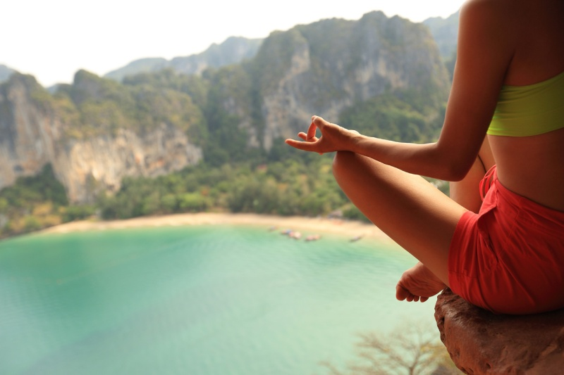woman_meditating_on_hill_top_next_to_a_beach